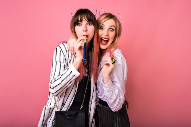 Cerrar retrato positivo de dos mujeres hipster felices divirtiéndose, usando accesorios de fiesta, retrato loco de cerca, tiempo de amistad