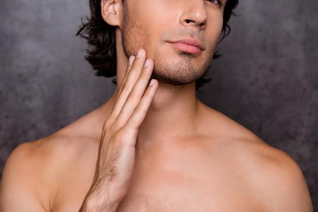 Cerrar retrato recortado de chico desnudo tocando la barbilla