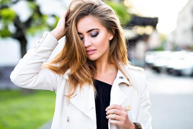 Cerrar retrato de sexy chica rubia increíble posando en el centro de la ciudad de europa, cerrar los ojos