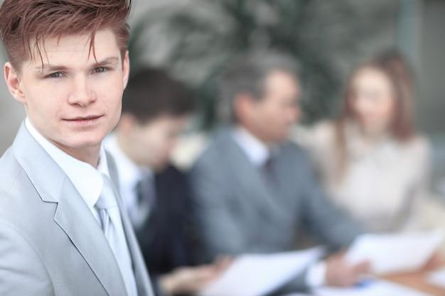 Cerrar el rostro de un joven empresario serio en la oficina de fondo borroso