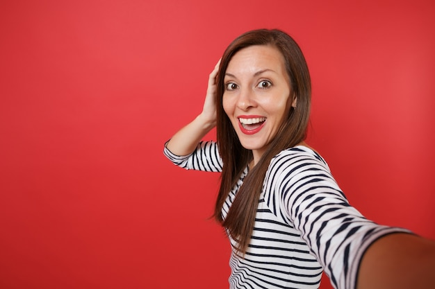 Cerrar selfie foto de mujer joven emocionada en ropa rayada manteniendo la boca abierta mirando sorprendido