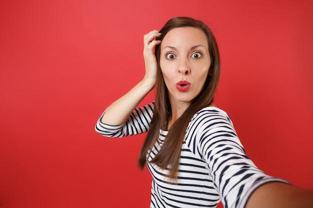 Cerrar selfie foto de sorprendida joven en ropa a rayas manteniendo la mano cerca de la cabeza, mirando asombrado