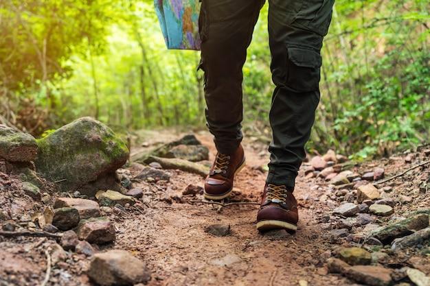 Cerrar senderismo hombre con botas de trekking caminando en el bosque