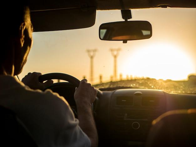 Cerrar la silueta del hombre conduciendo un coche en una puesta de sol durante la hora dorada