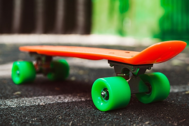 Cerrar skateboard penny naranja sobre asfalto detrás de la pared verde