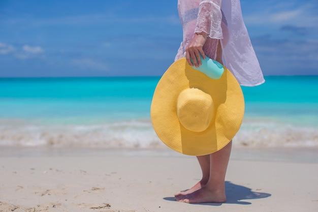 Cerrar un sombrero y crema solar en manos de mujeres