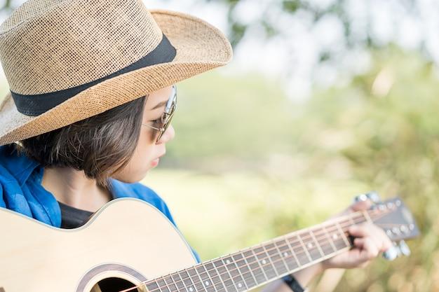 Cerrar sombrero de ropa de mujer y tocar la guitarra