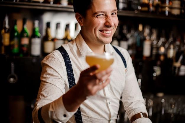 Cerrar sonriente barman con cóctel de naranja