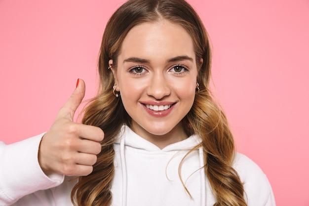 Cerrar sonriente mujer rubia vestida con ropa casual mostrando el pulgar hacia arriba y mirando al frente sobre la pared rosa