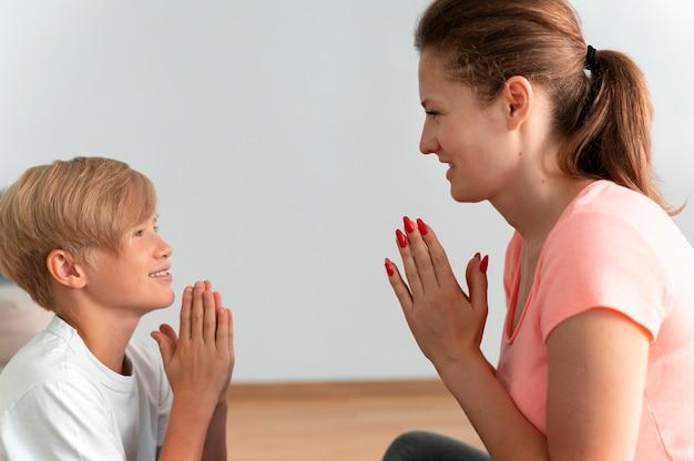Cerrar sonriente niño y mujer meditando