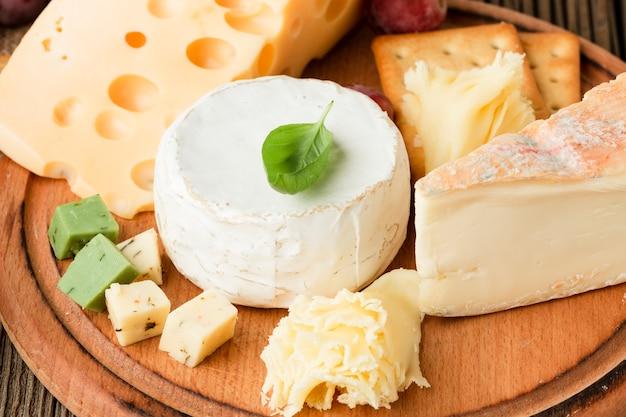 Cerrar surtido de quesos gourmet en tabla de cortar de madera