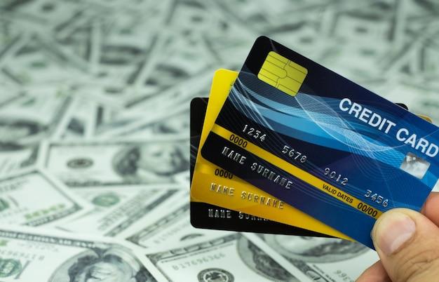 Cerrar tarjeta de crédito aislada en la pila de billetes de dinero de fondo de 100 usd