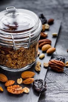 Cerrar tarro de avena con fechas y mezcla de nueces