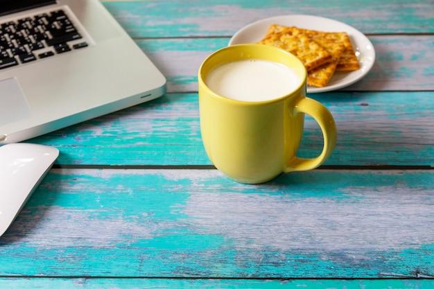 Cerrar una taza amarilla de leche fresca con un portátil, un ratón y una galleta en la mesa de madera