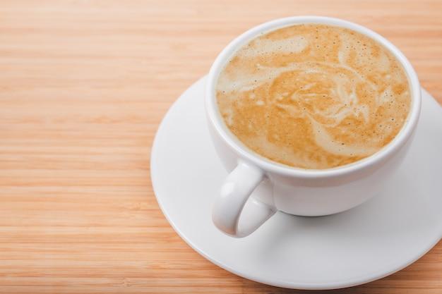 Cerrar la taza de café con leche con arte latte en la mesa de madera en el café