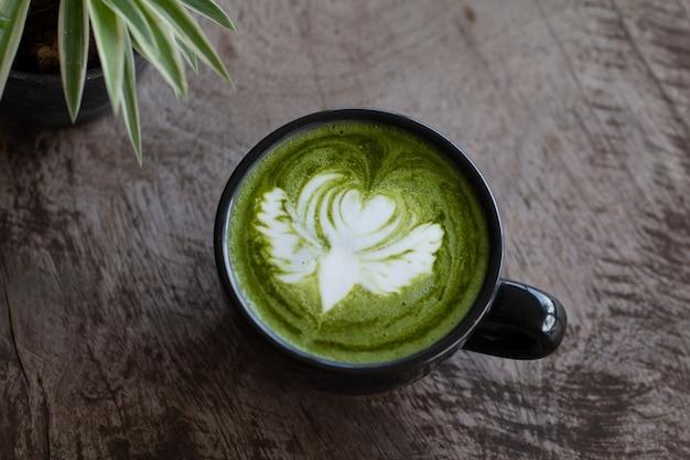 Cerrar una taza de té verde matcha bebida caliente de arte tardío en la mesa de madera