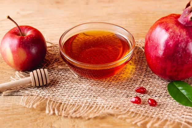 Cerrar tazón de miel con cucharón y frutas