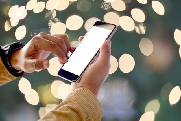 Cerrar el teléfono móvil con pantalla en blanco en la mano del hombre en el fondo borroso de luz bokeh de navidad