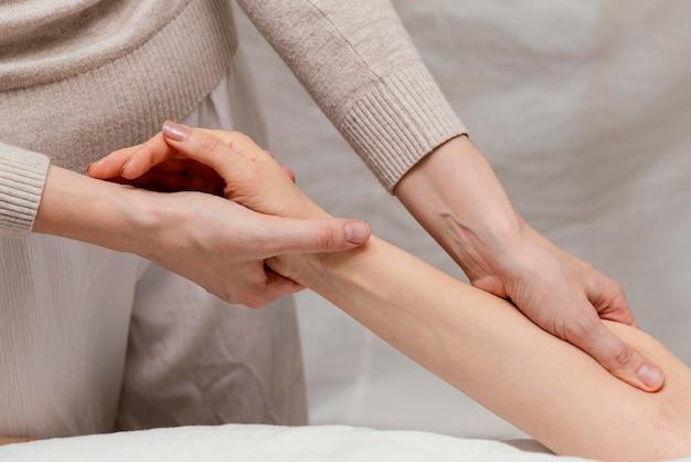 Cerrar terapeuta masajeando el brazo del paciente