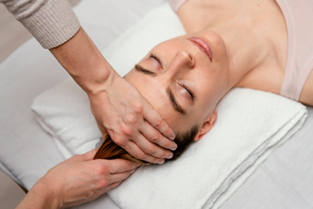 Cerrar terapeuta masajeando el cabello del paciente
