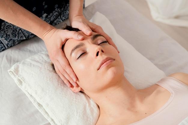 Cerrar terapeuta masajeando la cabeza del paciente