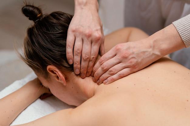 Cerrar terapeuta masajeando el cuello