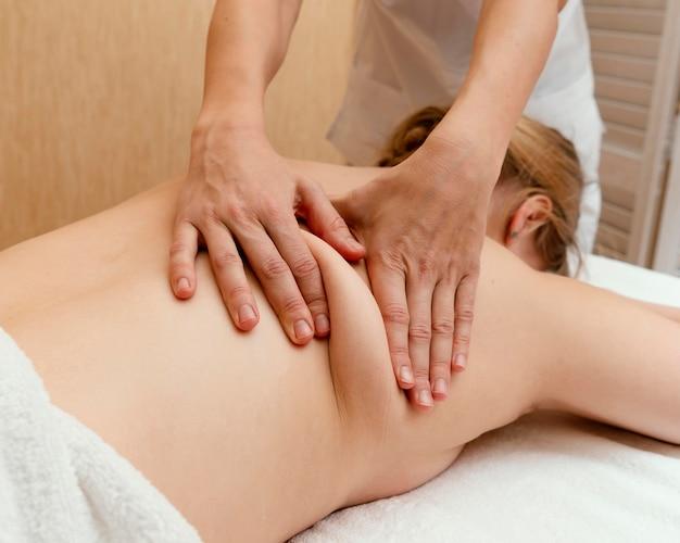 Cerrar terapeuta masajeando la espalda de la mujer