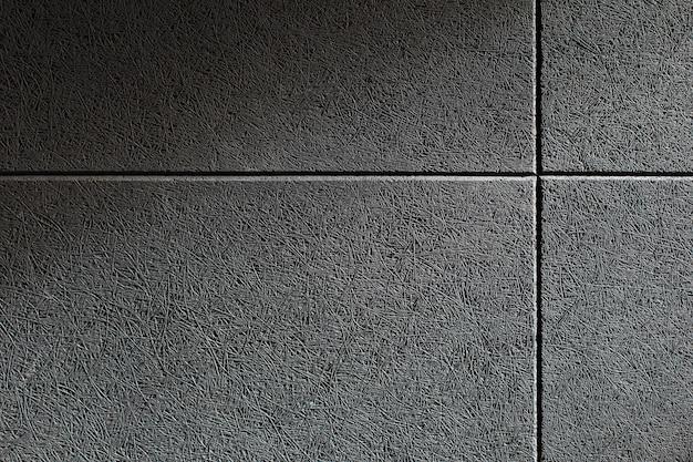 Cerrar la textura de una pared con un panel de absorción de sonido gris montado en él