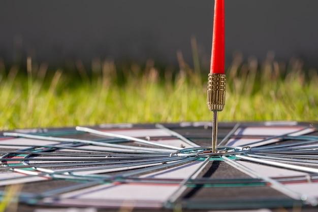 Cerrar tiro flecha de dardo rojo golpeando en el centro de destino del tablero de dardos, objetivo de negocio o concepto de éxito de destino.