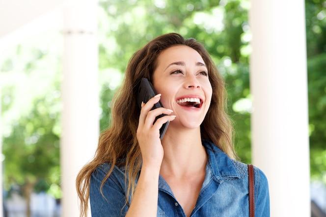 Cerrar una joven mujer fuera hablando por teléfono móvil