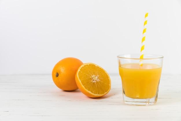 Cerrar el vaso de jugo de naranja con paja