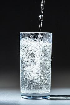 Cerrar vertiendo agua de bebida fresca purificada de la botella en la mesa