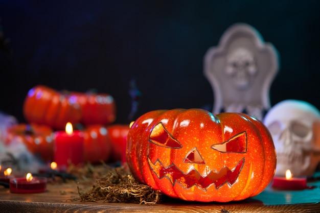 Cerrar vista de calabaza naranja aterradora sobre una mesa de madera para la celebración de halloween. cráneo humano espeluznante.