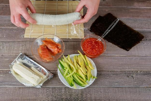 Cerrar vista de cocineros manos torciendo estera con ingredientes