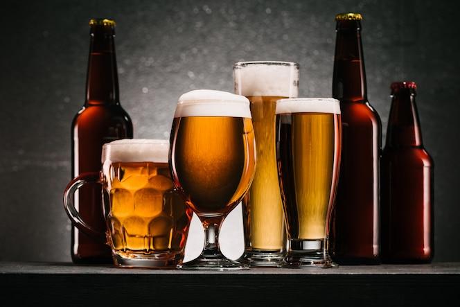 Cerrar vista de botellas y jarras de cerveza sobre fondo gris