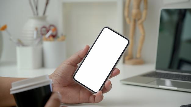 Cerrar vista de diseñador con smartphone de pantalla en blanco y sosteniendo la taza de café