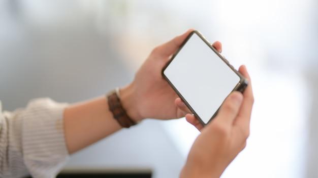 Cerrar vista de empresario enviando mensajes de texto en el teléfono inteligente mientras está sentado en el sofá