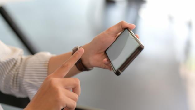 Cerrar vista de empresario tocando el teléfono inteligente horizontal