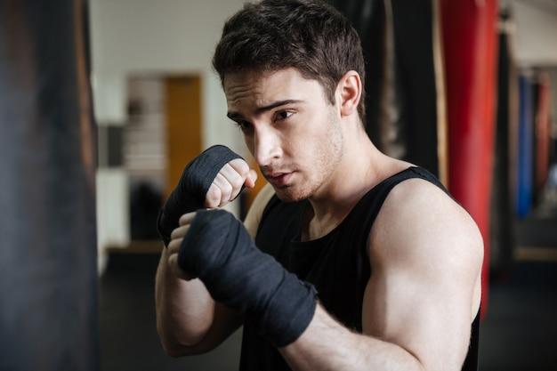 Cerrar vista de entrenamiento de boxeador con saco de boxeo