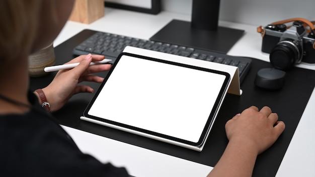 Cerrar vista de fotógrafa trabajando con tableta digital en la oficina creativa.