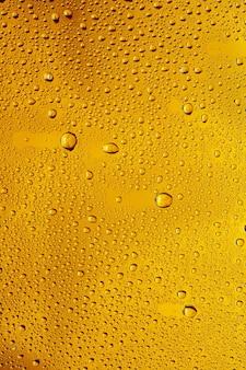Cerrar vista de gotas frías en el vaso de cerveza de fondo. textura de bebida alcohólica de enfriamiento con macro burbujas en la pared de vidrio. efervescente o flotando hasta la parte superior de la superficie. de color dorado.