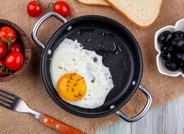 Cerrar vista de huevo frito en sartén con tenedor y tazón de rodajas de tomate y pan con aceitunas sobre tela de saco y superficie de madera