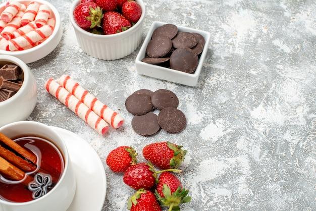 Cerrar vista inferior cuencos con fresas, chocolates, caramelos y té de semillas de anís y canela en el lado izquierdo del fondo blanco grisáceo