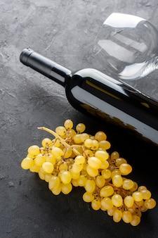 Cerrar vista inferior uvas amarillas frescas botella de vino y abridor de vino de vidrio en la mesa oscura
