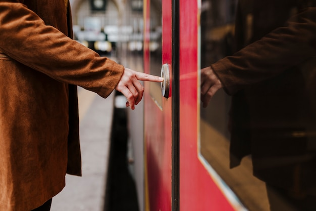 Cerrar vista de joven turista en la estación de tren esperando tomar un tren y viajar