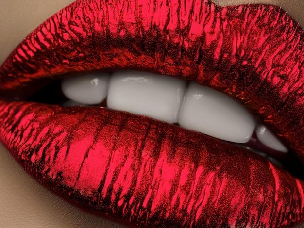 Cerrar vista de labios de mujer hermosa con lápiz labial rojo metálico