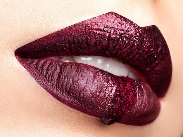 Cerrar vista de labios de mujer hermosa con lápiz labial rojo oscuro. maquillaje de moda. cosmetología