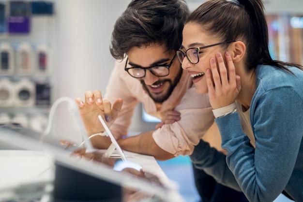 Cerrar vista lateral de bastante feliz emocionado hipster joven amor pareja prueba nuevos gadgets inteligentes en una tienda de tecnología.