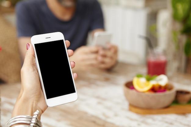 Cerrar vista de manos de mujer con uñas rojas con elegante pulsera con teléfono móvil