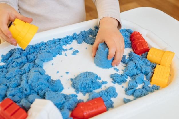 Cerrar vista de las manos del niño jugando con arena cinética. juego creativo infantil para el desarrollo temprano y la motricidad fina.